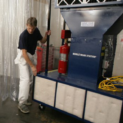 Painter moving portable automotive paint booth in body shop.