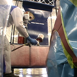 Painter in portable spray booth spraying auto fender.