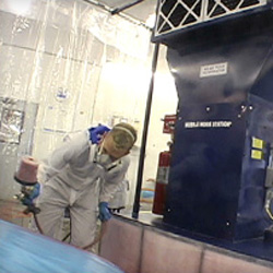 Painter spraying fender using portable paint booth in body shop.